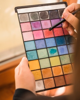 Woman's hand holding palette of eye shadow powder