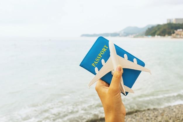 海の背景にパスポートとおもちゃの飛行機を持っている女性の手、旅行の概念