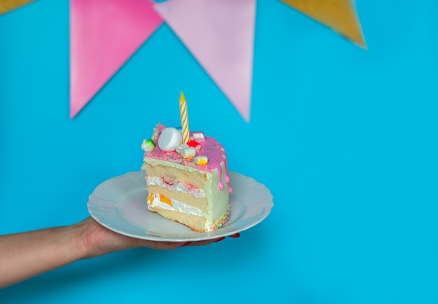 Woman's hand holding a piece of birthday cake on blue background with copy space