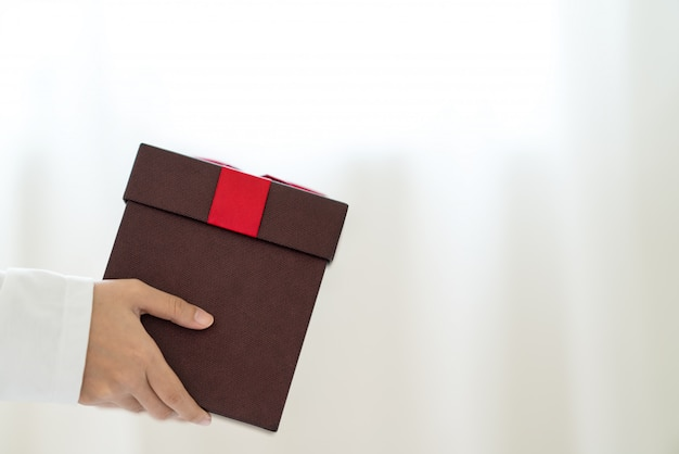 Woman's hand holding present red box