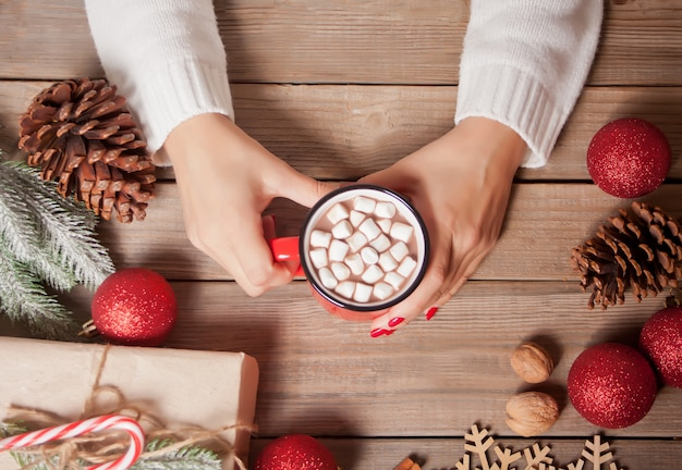 Woman's hand holding red mug of christmas cocoa with marshmallows.