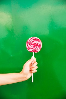 Woman's hand holding red and pink lollipop in hand against green background