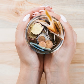 Woman's hand holding saving in the jar against wooden background