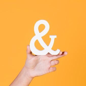 Женская рука держит знак на желтом фоне