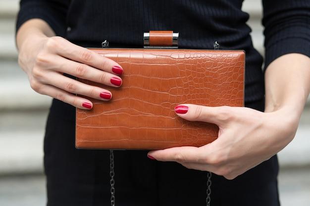 小さな革の茶色の財布を持っている女性の手