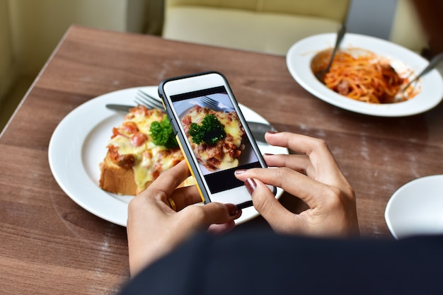 Woman's hand holding smart phone and take photo food on wooden table