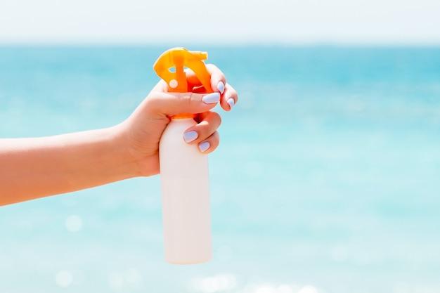 Woman's hand holding sunblock spray at the beach
