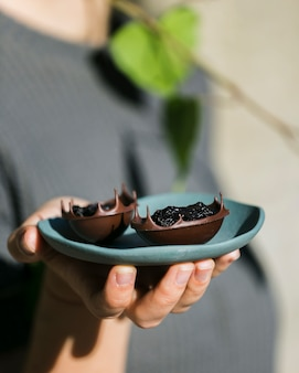 Woman's hand holding tasty dessert bowls in ceramic plate