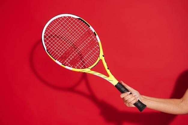テニスラケットを持っている女性の手