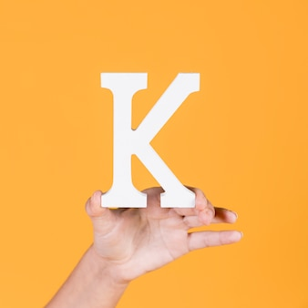 Woman's hand holding up the capital alphabet k