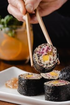 Женская рука держит веганский суши-ролл деревянными палочками для еды