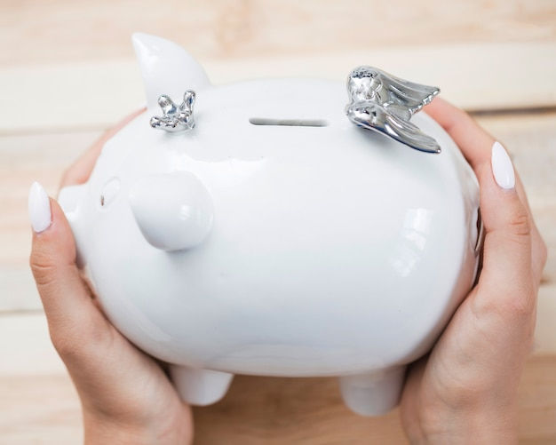 Woman's hand holding white ceramic piggybank with silver crown and wings