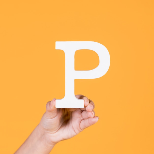 Woman's hand holding the white letter p
