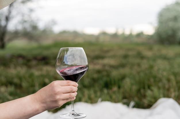 Женская рука держит бокал с красным вином
