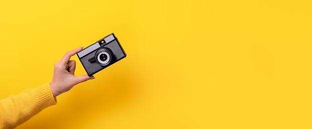 여자의 손을 노란색에 오래 된 필름 카메라를 보유