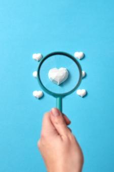 女性の手は、とりわけ心臓の焦点を合わせた石膏像の上に大きな虫眼鏡を持っています