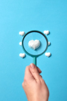 Woman's hand holds big magnifying glass above focused plaster figure of heart among others