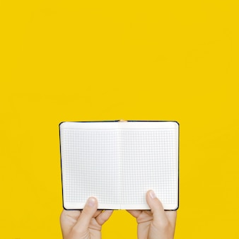 A woman's hand holds a blue closed notebook on a bright yellow wall.