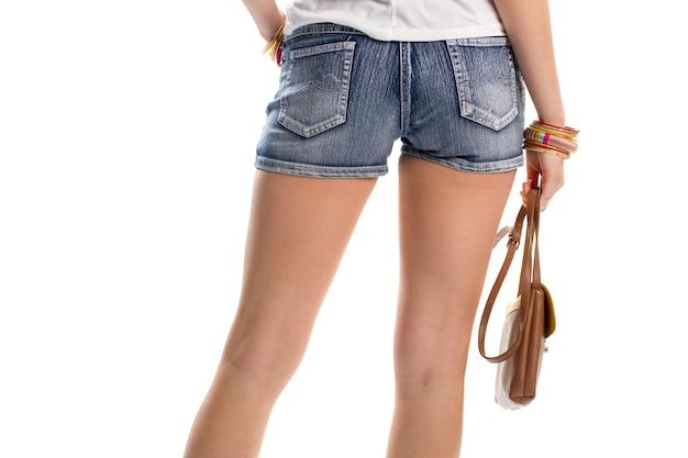 여자의 손에는 갈색 가방이 있습니다. 데님 반바지의 뒷모습. 트렌디한 핸드백과 팔찌. 새로운 액세서리 세트입니다.