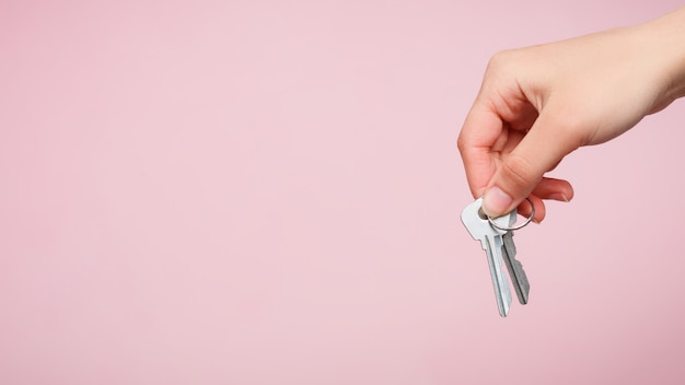 A woman's hand holds a bunch of keys.