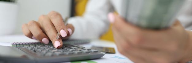 Женская рука держит доллары и ручку другой рукой и вводит числа на калькуляторе