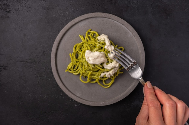 Woman's hand holds a fork with a paste with strachatella and pesto, selective focus, top view