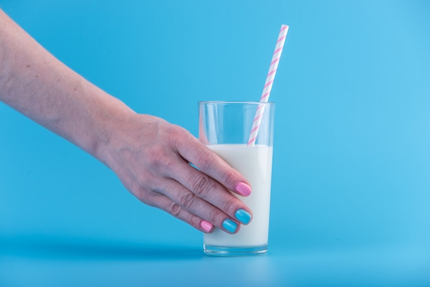 Woman's hand holds glass of fresh milk with a straw on a blue background. concept of healthy dairy products with calcium