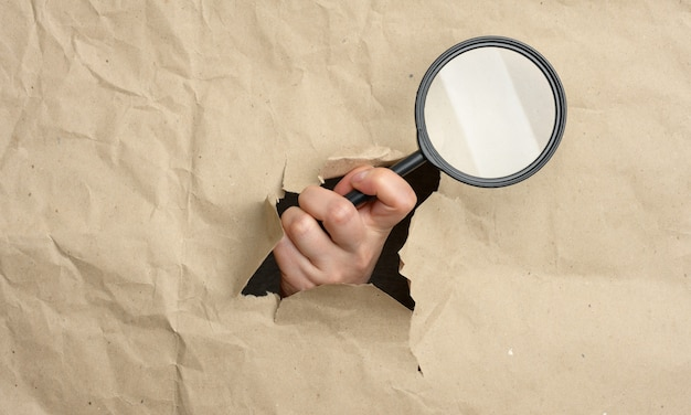 A woman's hand holds a glass magnifier, part of the body sticks out of a hole in brown paper. solution search concept, research