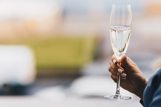 Woman`s hand holds glass of white wine, celebrates something together with friends, blurred background