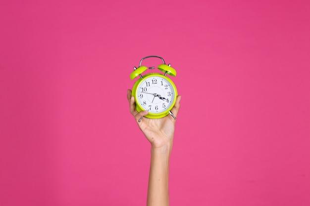 Woman's hand holds green alarm clock