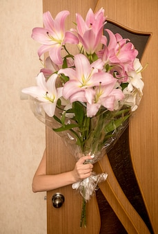 A woman's hand holds a large beautiful bouquet of pink lilies behind a brown door.
