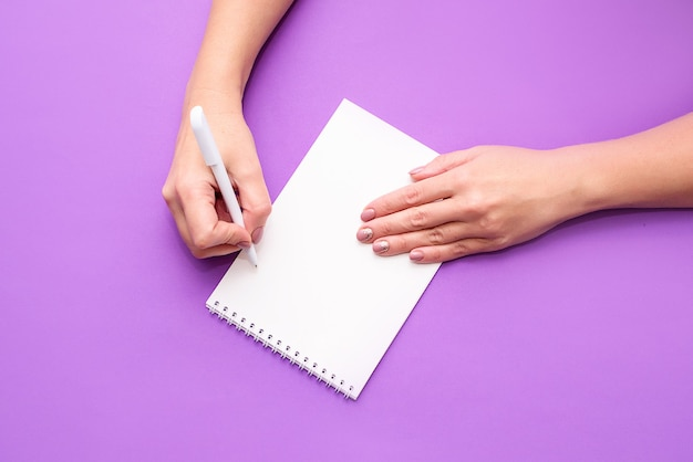 A woman's hand holds a notebook with white sheets on a light background. a place for text, a view from above. flat lay