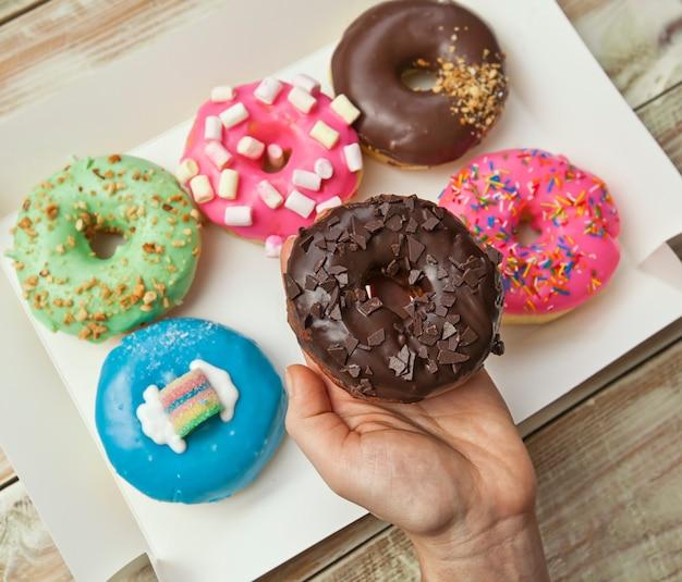Женская рука держит один пончик над коробкой с разными пончиками на деревянном столе