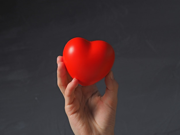 A woman's hand holds a red heart on a gray background with her fingers. concert of health, love, valentine's day