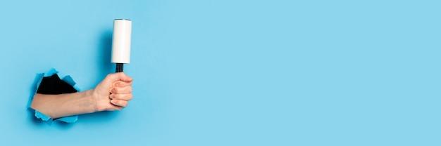 Женская рука держит ролик для чистки одежды на синем фоне