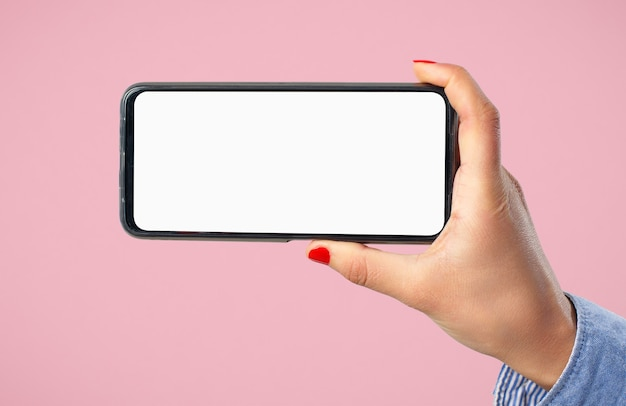 A woman's hand holds a smartphone with a blank white screen horizontally. against a pink background.