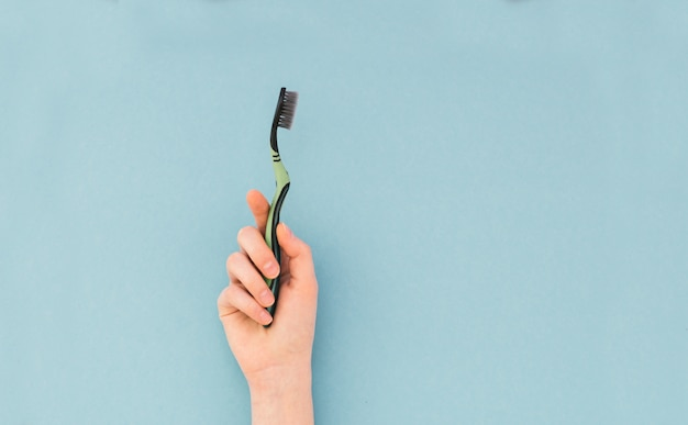 Woman's hand holds a toothbrush on blue
