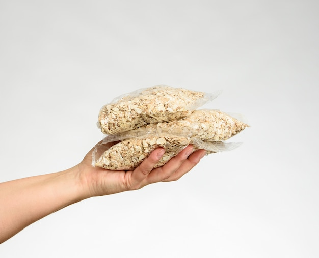Woman's hand holds a transparent bag with oatmeal, white background