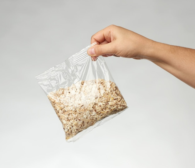 Woman's hand holds a transparent bag with oatmeal
