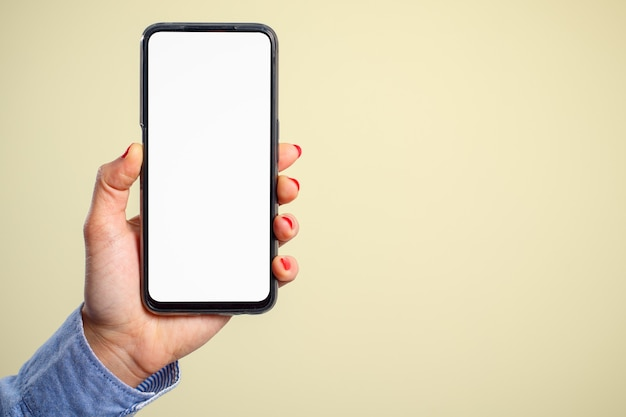 A woman's hand holds vertically a smartphone with a blank white screen on a cream background. for the copyspace.