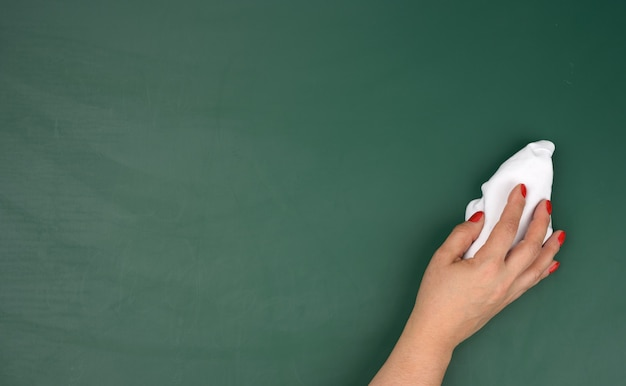 A woman's hand holds a white rag against the background of a green chalk board, a place for an inscription