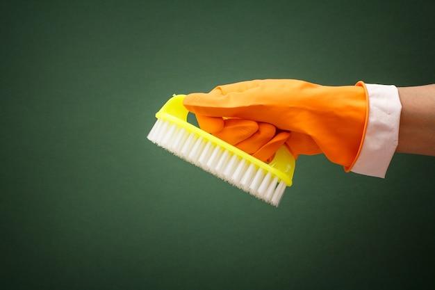 녹색 배경에 브러시와 주황색 보호 장갑에 여자의 손. 세척 및 청소 개념입니다.