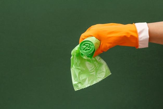 녹색 배경에 쓰레기 봉투와 함께 주황색 보호 장갑에 여자의 손. 세척 및 청소 개념입니다.
