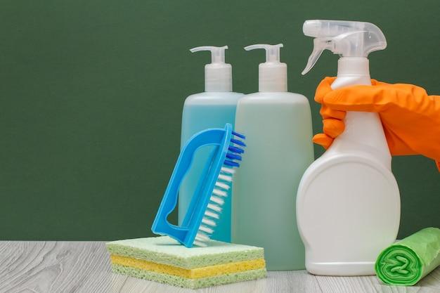 ガラスとタイルクリーナーのプラスチックボトル、洗剤のボトルと緑の背景のブラシとオレンジ色の保護手袋で女性の手。製品の洗浄と洗浄。
