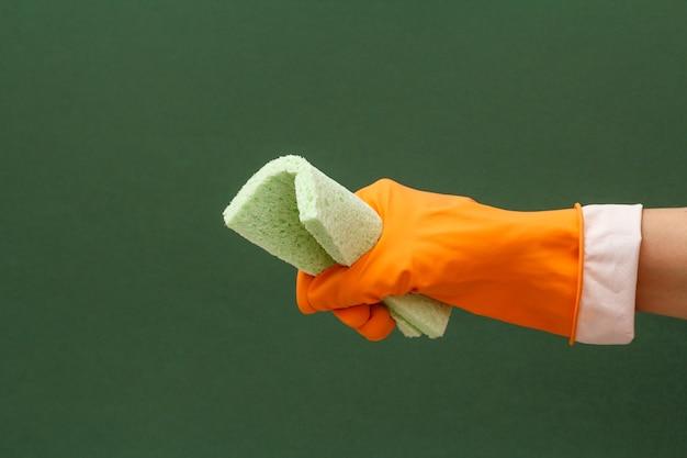 녹색 배경에 스폰지와 오렌지 보호 장갑에 여자의 손. 세척 및 청소 개념입니다.