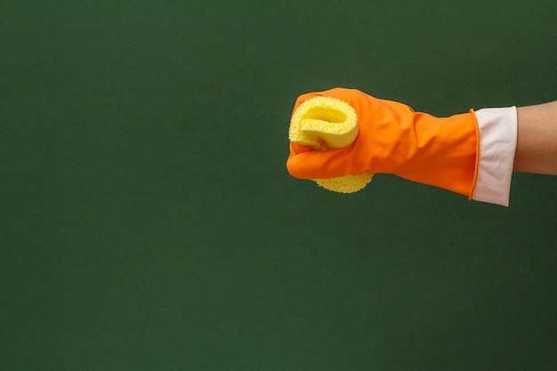 녹색 배경에 노란색 스폰지가 있는 주황색 보호 장갑을 끼고 있는 여성의 손. 세척 및 청소 개념입니다.