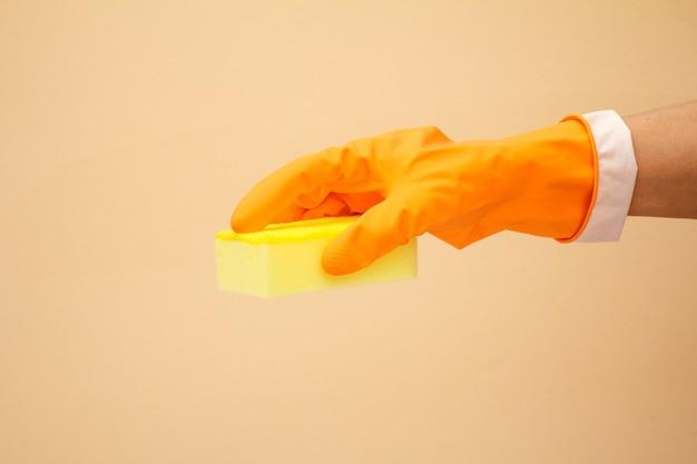 베이지색 바탕에 스폰지와 오렌지 고무 장갑에 여자의 손. 세척 및 청소 개념입니다.