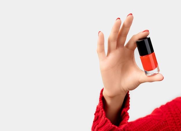 マニキュア液のボトルを保持している赤いマニキュアとセーターの女性の手