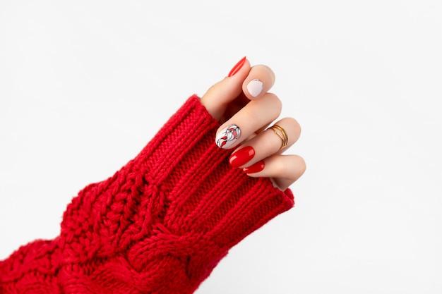 회색에 빨간 매니큐어와 스웨터에 여자의 손