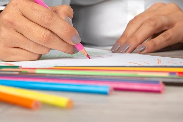 사무실에서 여자의 손을 종이에 크레용으로 그립니다.